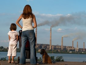 Mother and daughter watch factories causing air pollution