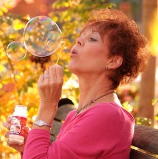 Breast cancer survivor blowing a bubble