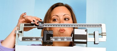 Woman checking her weight gain on a scale