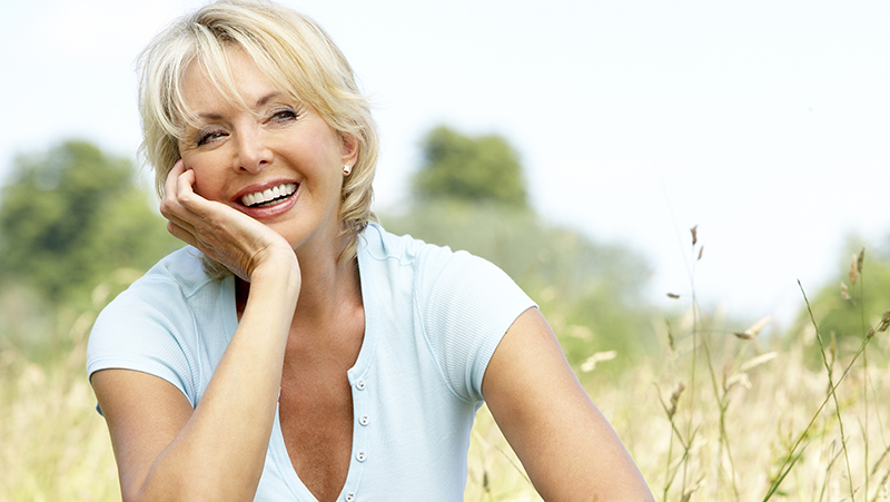 Menopausal woman sitting outside and smiling