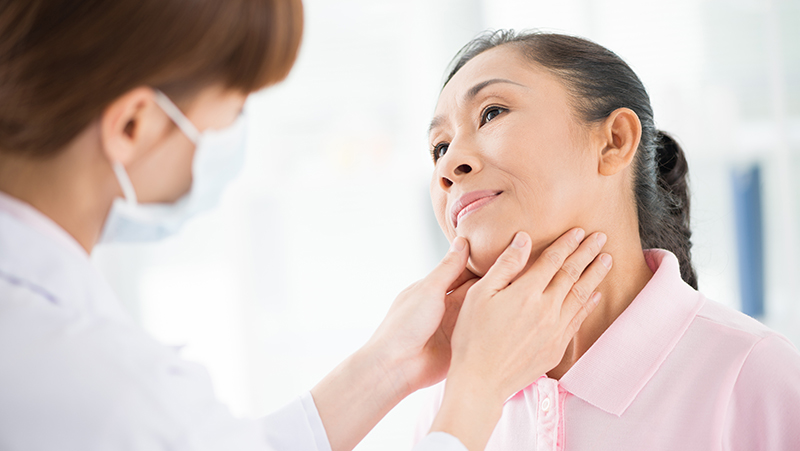 Doctor checking patient's thyroid gland