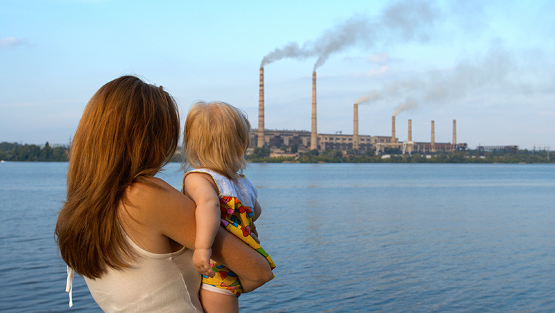 Mother and child watch factories causing air pollution