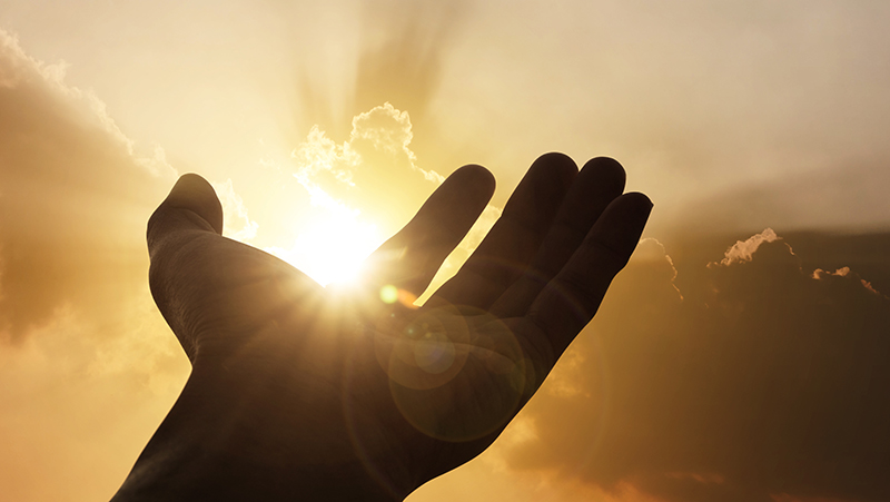 Silhouette of a hand with sun shining through