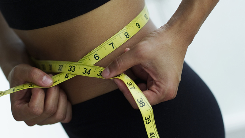 Woman checking weight loss by measuring stomach