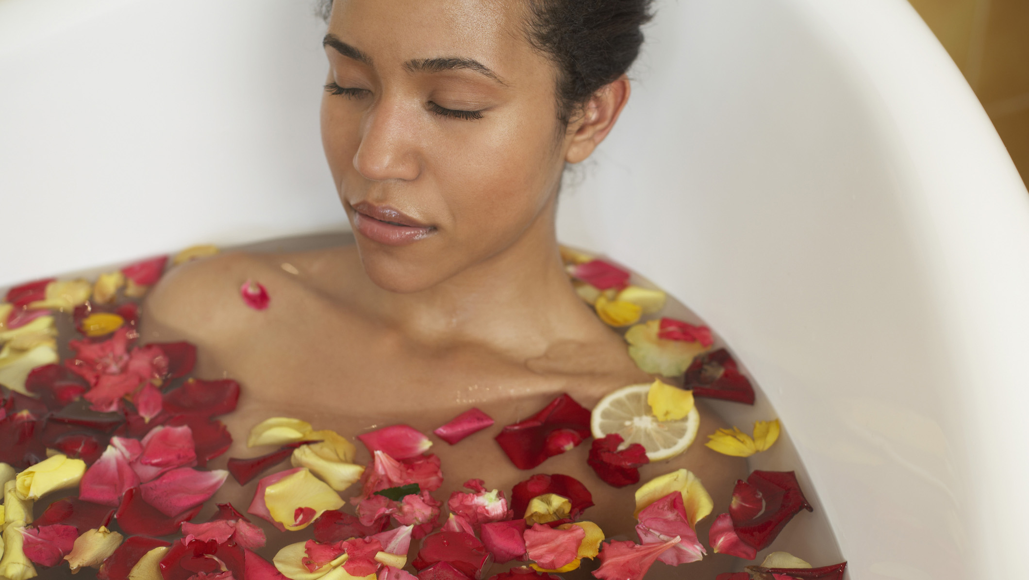 Woman relaxes in bath of flower petals