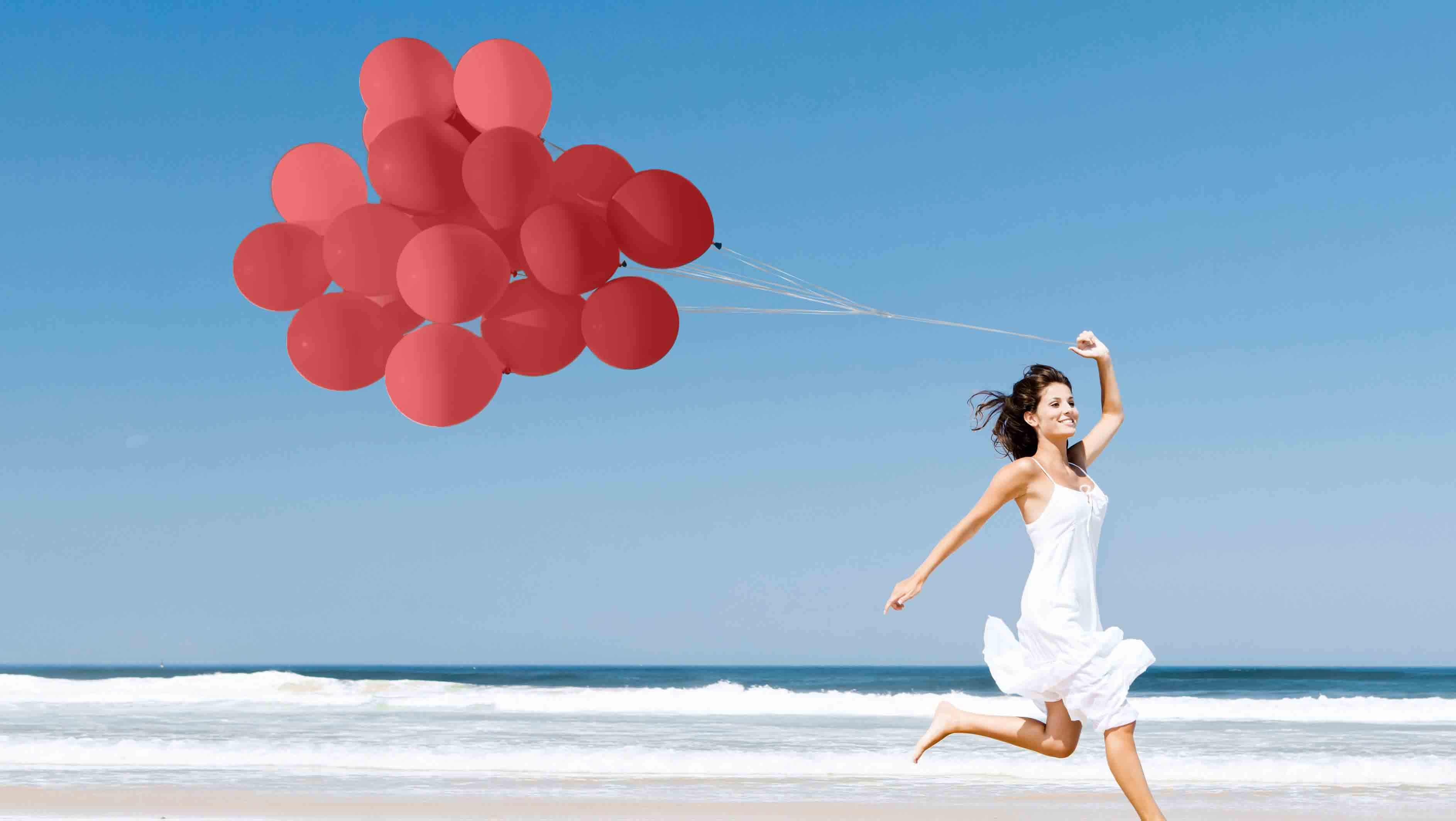 Woman runs down the beach holding red balloons