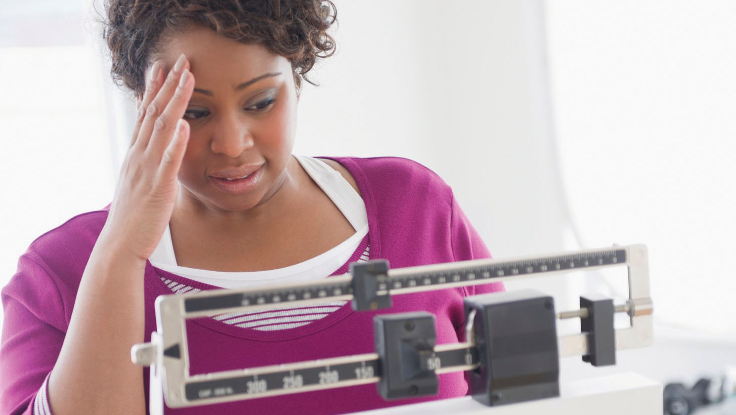 Woman checking weight loss on scale