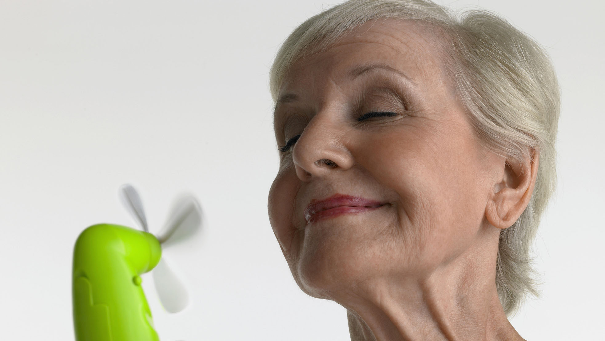 Mature woman using fan to cool down her hot flashes