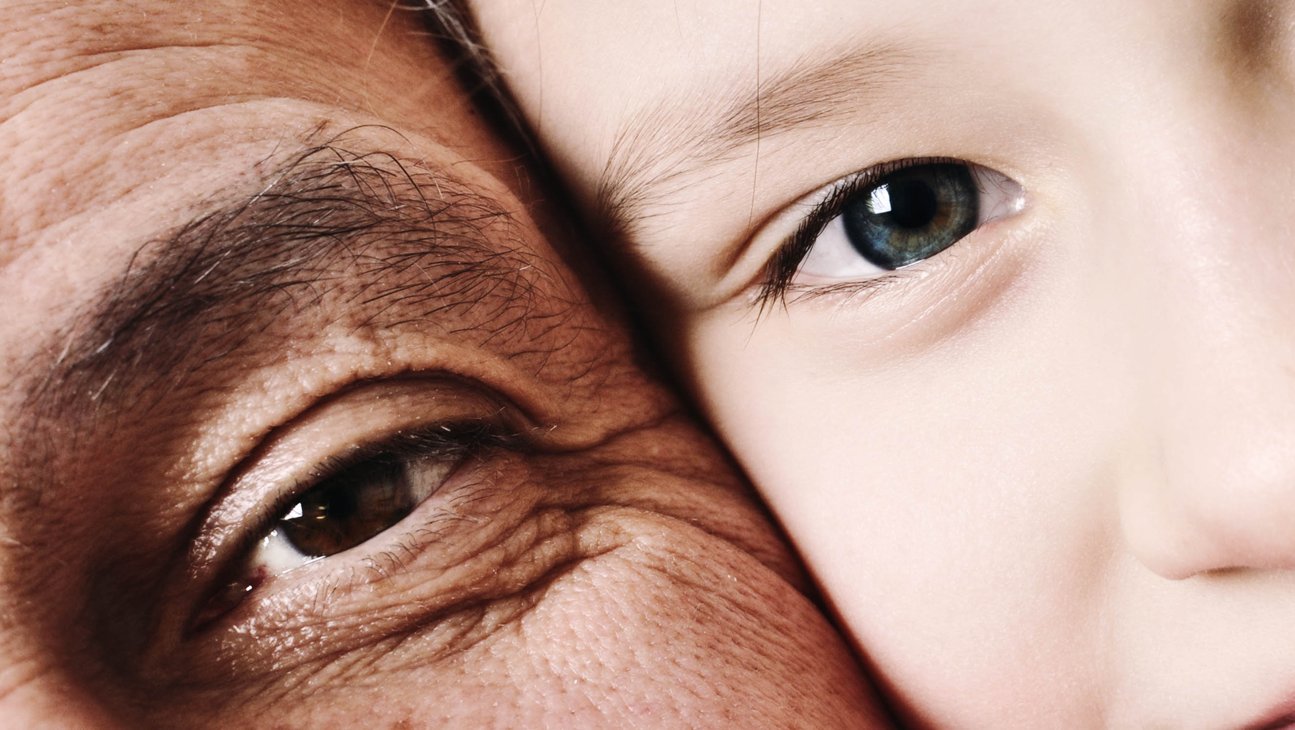 Person with aging skin next to child with young skin