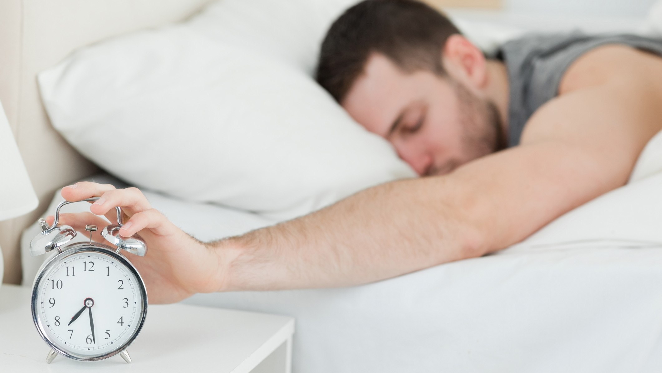 Man laying in bed turning off his alarm