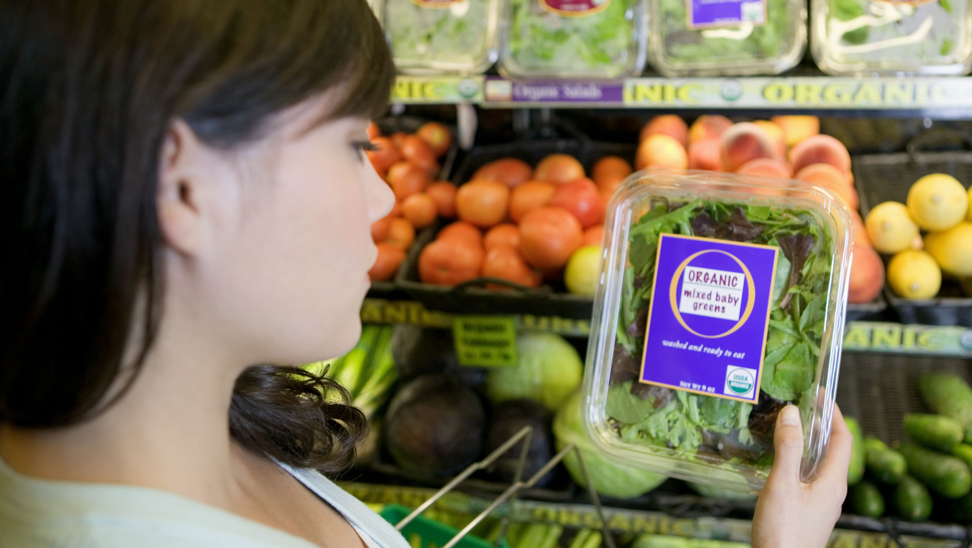 Woman looking at organic greens in the grocery store
