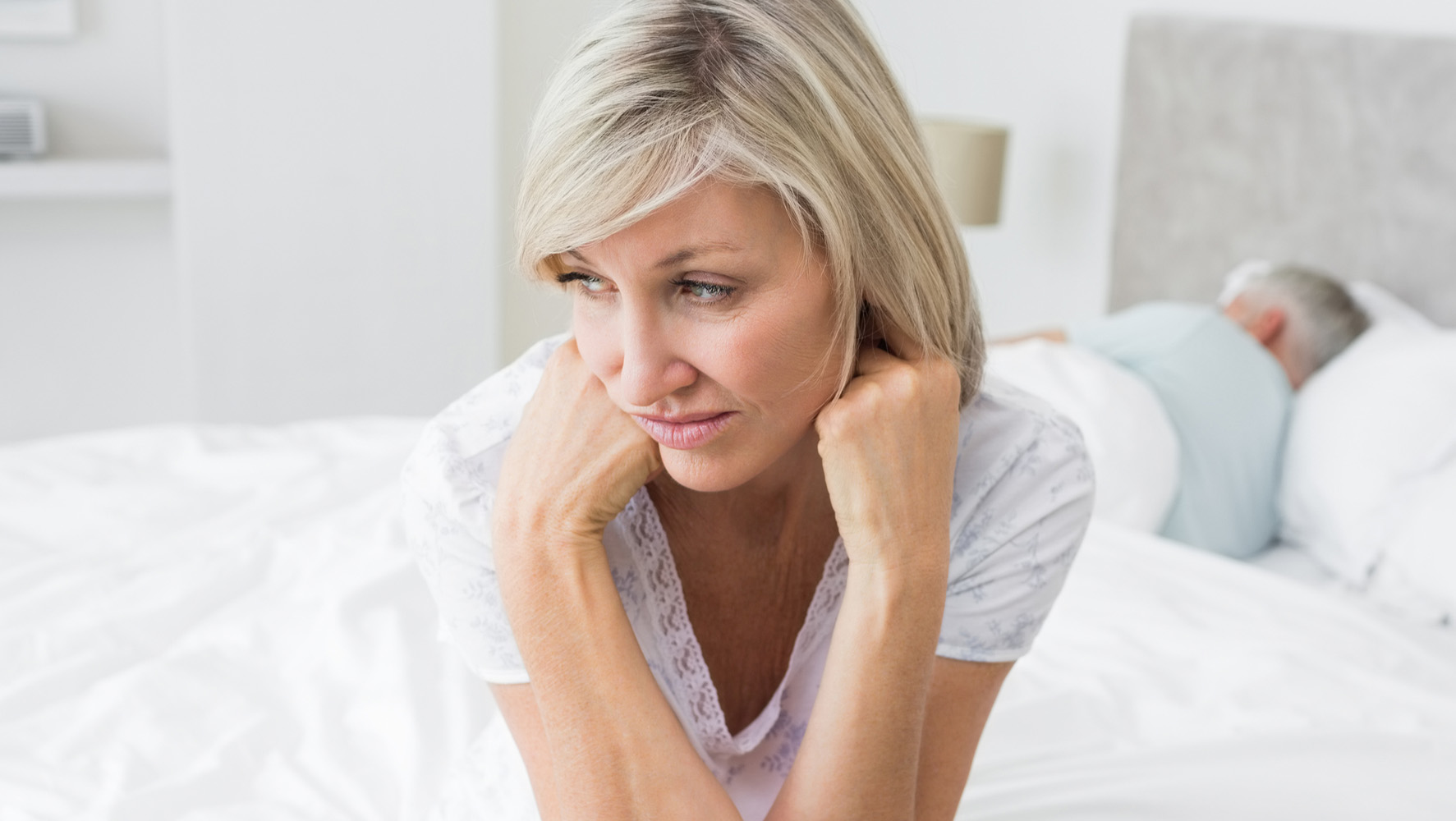 Woman sitting up in bed with partner sleeping behind her