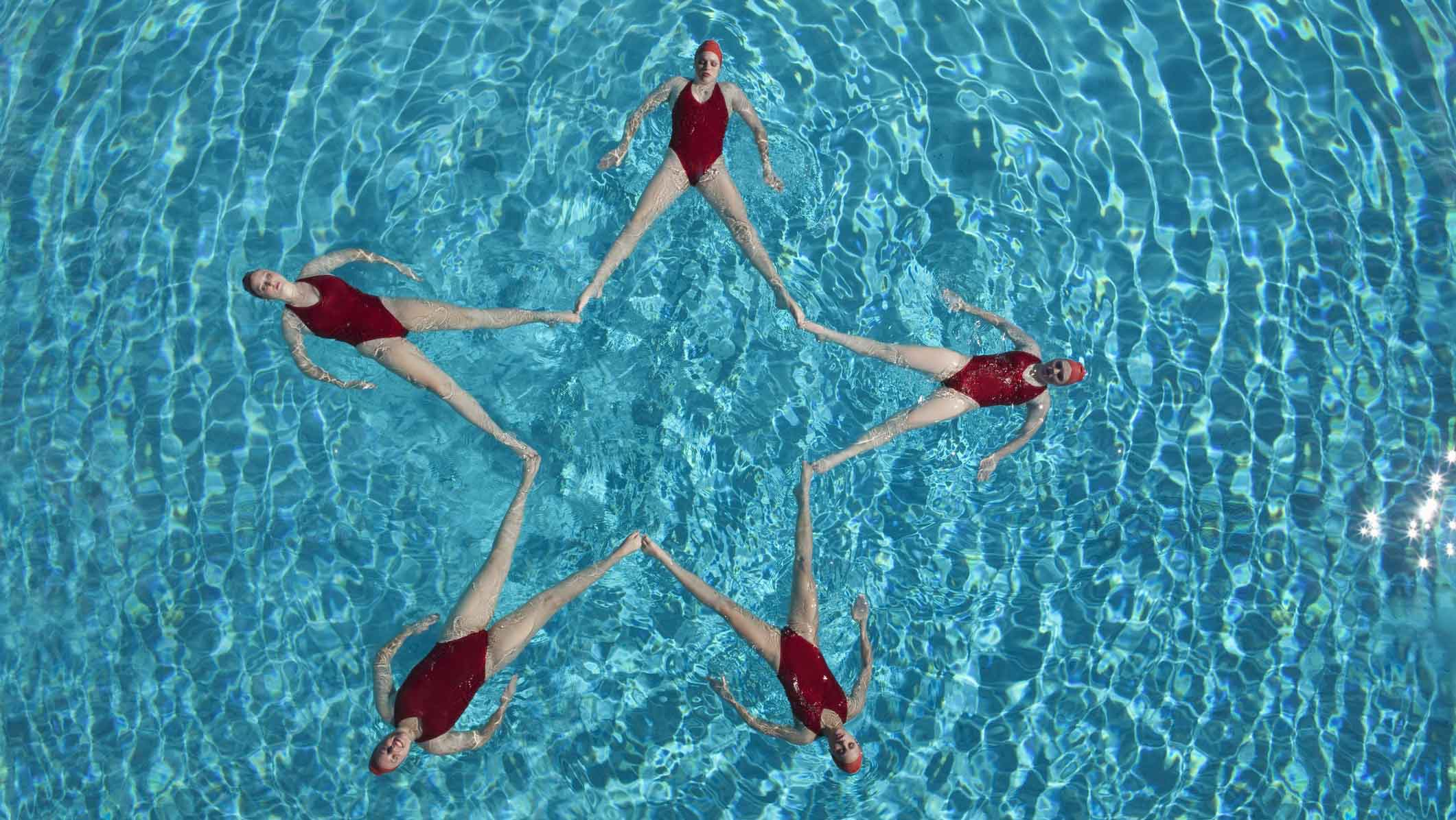 Synchronized swimmers making a star shape in the pool