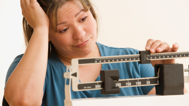 Woman stressed over weight management checks the scale