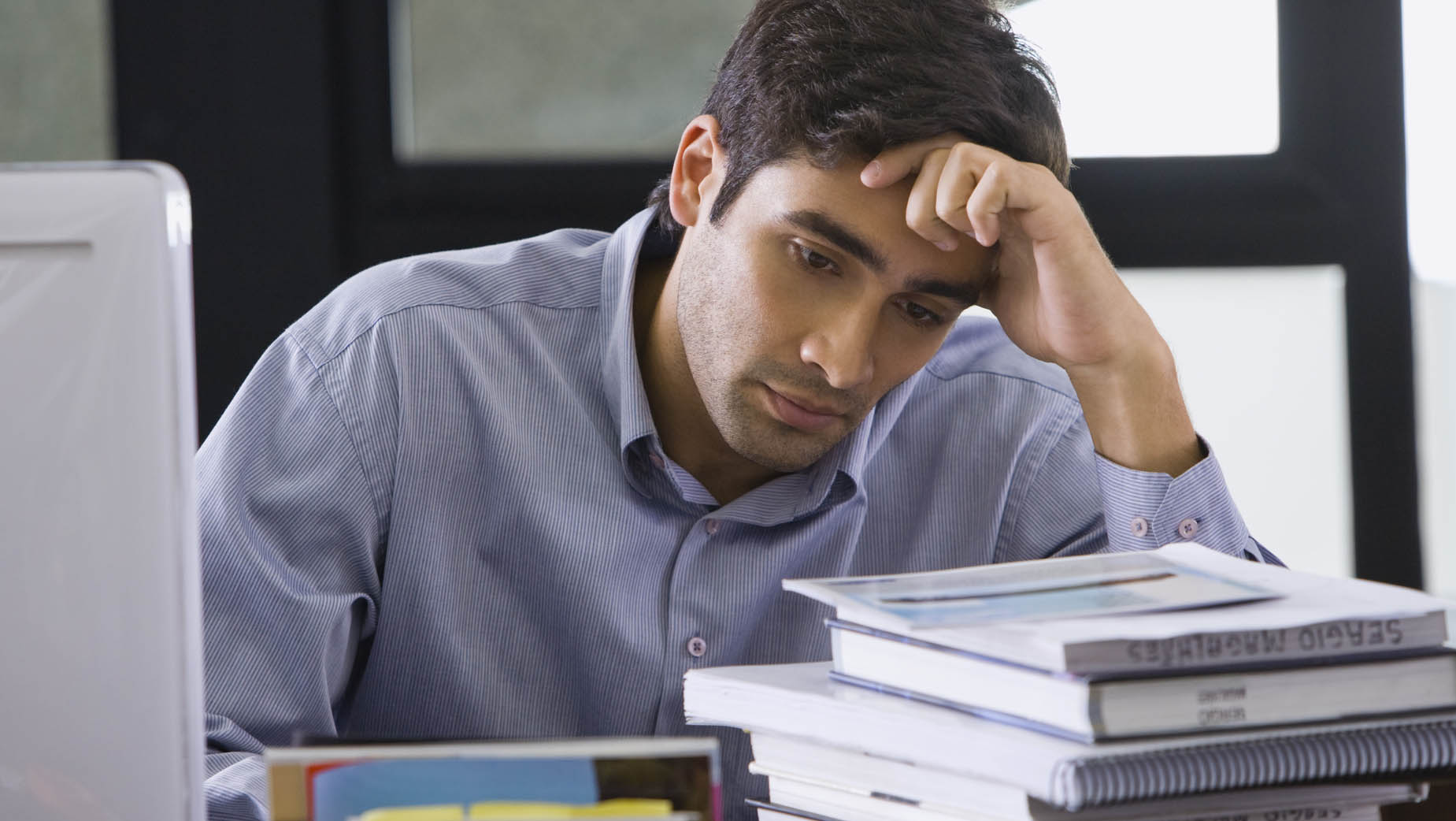Stressed man resting forehead on hand