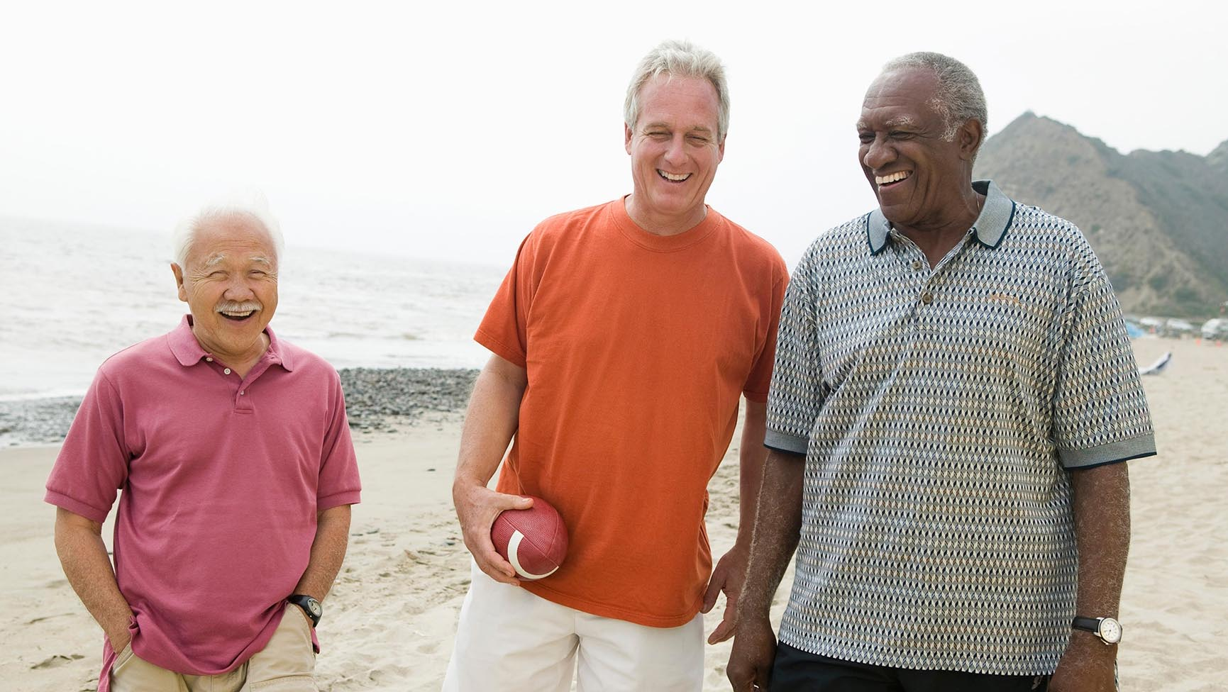 Mature men playing football on the beach