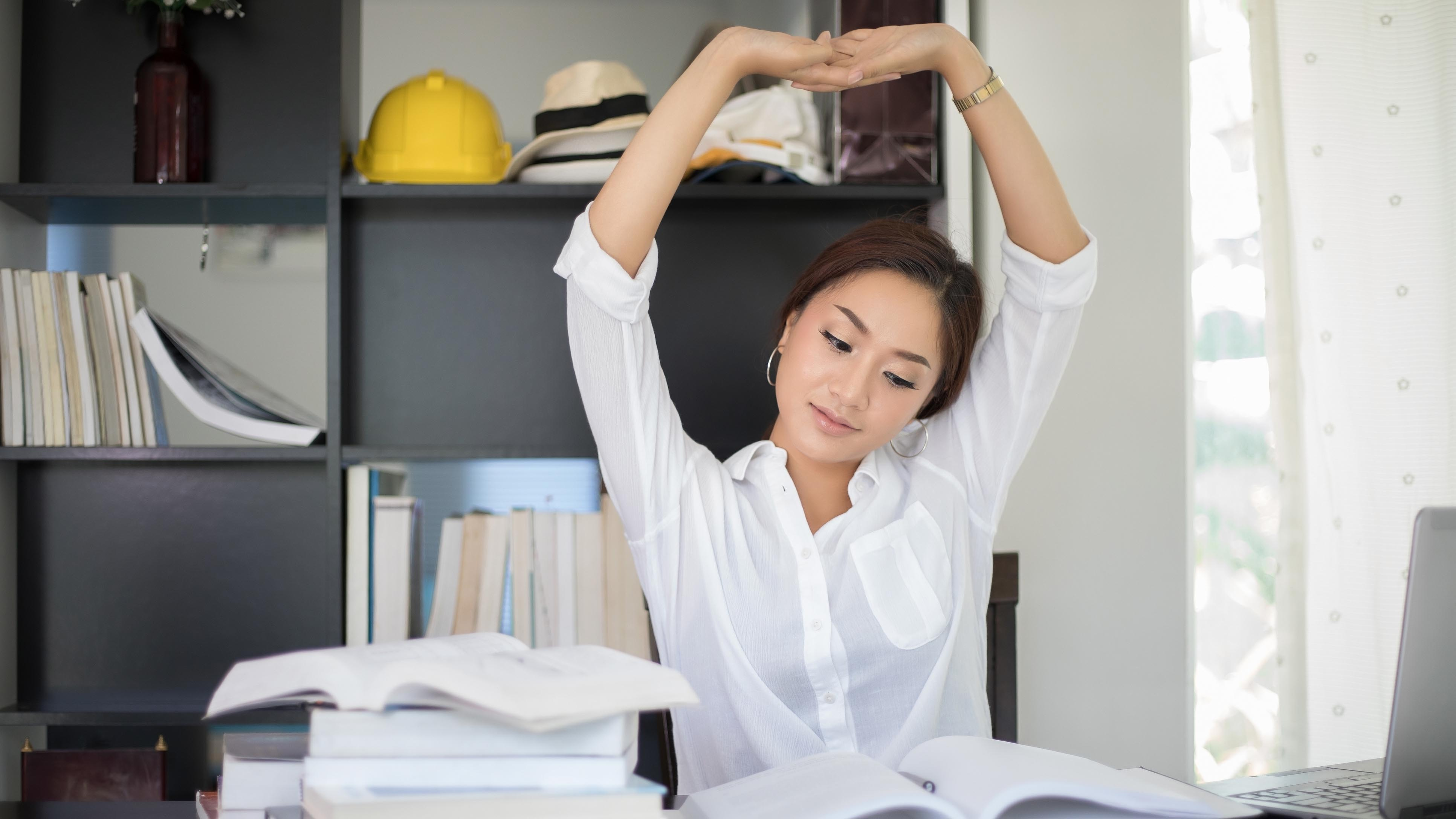 Professional woman stretching at desk